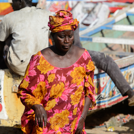 KAYAR, SENEGAL - APR 27, 2017: Unidentified Senegalese woman in traditional clothes walks on the coast of the Atlantic Ocean. Many Kayar people work in port Editorial