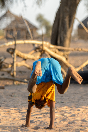 FERLO DESERT, SENEGAL - APR 25, 2017: Unidentified Fulani little boy stands on his arms on the ground. Fulanis (Peul) are the largest tribe in West African savannahs