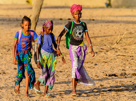 FERLO DESERT, SENEGAL - APR 25, 2017: Unidentified Fulani people walk along the street. Fulanis (Peul) are the largest tribe in West African savannahs