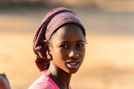 FERLO DESERT, SENEGAL - 25 APRILE 2017: Donna Fulani non identificata in velo si trova sulla strada. I Fulanis (Peul) sono la tribù più numerosa delle savane dell'Africa occidentale