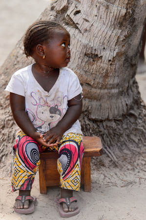 KASCHOUANE, SENEGAL - APR 29, 2017: Unidentified Diola little girl with braids sits on the chair in Kaschouane village. Diolas are the ethnic group predominate in the region of Casamance