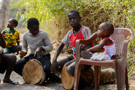 KASCHOUANE, SENEGAL - APR 29, 2017: Unidentified Diola boy plays on drums in Kaschouane village. Diolas are the ethnic group predominate in the region of Casamance Editorial