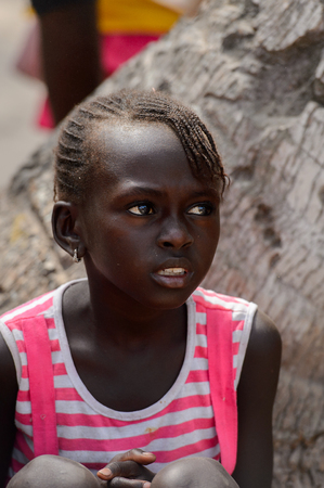 KASCHOUANE, SENEGAL - APR 29, 2017: Unidentified Diola little girl with braids sits  in Kaschouane village. Diolas are the ethnic group predominate in the region of Casamance
