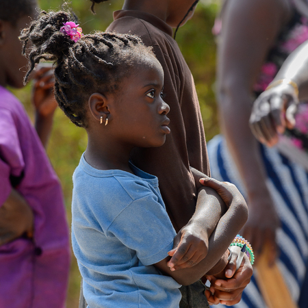 KASCHOUANE, SENEGAL - APR 29, 2017: Unidentified Diola little girl with braids holds her sisters hand  in Kaschouane village. Diolas are the ethnic group predominate in the region of Casamance