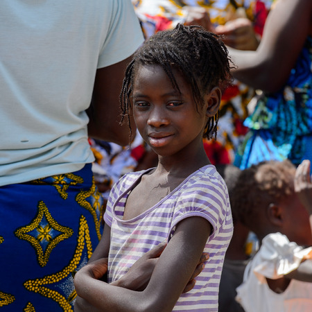 KASCHOUANE, SENEGAL - APR 29, 2017: Unidentified Diola little girl with braids smiles in Kaschouane village. Diolas are the ethnic group predominate in the region of Casamance