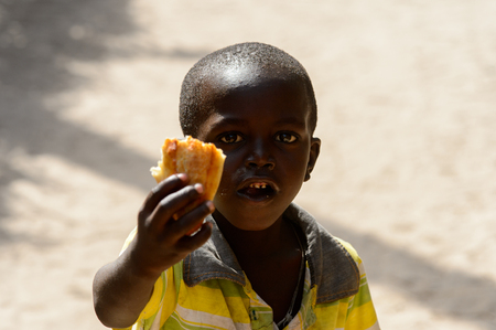 KASCHOUANE, SENEGAL - APR 29, 2017: Unidentified Diola little boy holds some food in his hand in Kaschouane village. Diolas are the ethnic group predominate in the region of Casamance