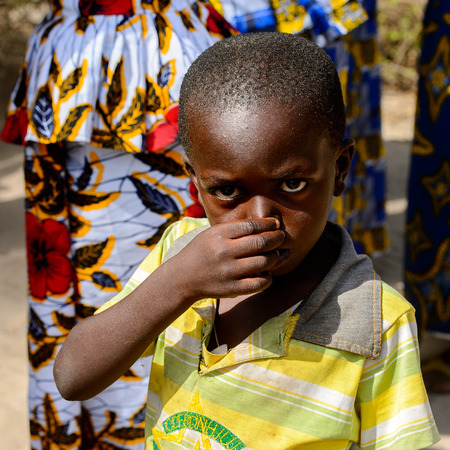 KASCHOUANE, SENEGAL - APR 29, 2017: Unidentified Diola little boy wipes his nose in Kaschouane village. Diolas are the ethnic group predominate in the region of Casamance Editorial