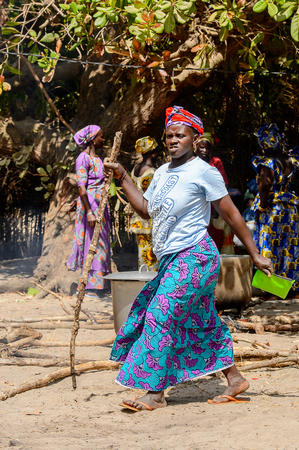 KASCHOUANE, SENEGAL - APR 29, 2017: Unidentified Diola   woman in traditional clothes walks along the street Kaschouane village. Diolas are the ethnic group predominate in the region of Casamance