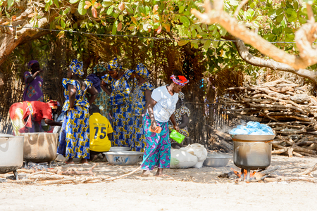 KASCHOUANE, SENEGAL - APR 29, 2017: Unidentified Diola women in traditional clothes stand on the street in Kaschouane village. Diolas are the ethnic group predominate in the region of Casamance Standard-Bild - 103810262