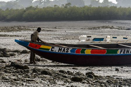 ORANGO ISLAND, GUINEA BISSAU - MAY 3, 2017: Unidentified local man stands near the boat on the coast of the Orange island, part of the Bijagos Archipelago.