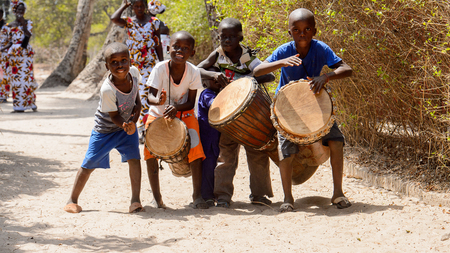 KASCHOUANE, SENEGAL - APR 29, 2017: Unidentified Diola little boys play the drums in Kaschouane village. Diolas are the ethnic group predominate in the region of Casamance Editorial