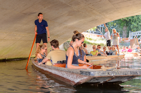 CAMBRIDGE, ENGLAND - JULY 19, 2016: Unidentified people in a boat over the river Cam under a bridge, Cambridge, England. The original name was the Granta river