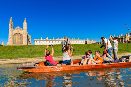 CAMBRIDGE, ENGLAND - JULY 19, 2016: Unidentified people in a boat near Trinity College over the river Cam, Cambridge, England. The original name was the Granta river