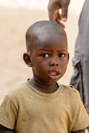 ORANGO ISLAND, GUINEA BISSAU - MAY 3, 2017: Unidentified local little boy looks ahead in the Etigoca village. People in G.-Bissau suffer of poverty due to the bad economy Editorial