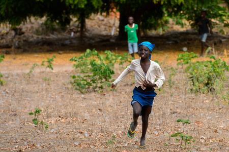 SOGA, GUINEA BISSAU - MAY 5, 2017: Unidentified local little girl runs along the street in a village of the Soga island. People in G.-Bissau still suffer of poverty Editorial