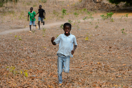 SOGA, GUINEA BISSAU - MAY 5, 2017: Unidentified local little boy runs along the street in a village of the Soga island. People in G.-Bissau still suffer of poverty Editorial