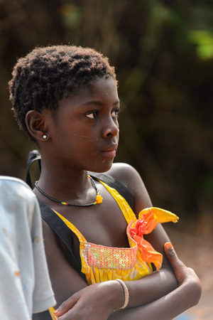 SOGA, GUINEA BISSAU - MAY 5, 2017: Unidentified local girl in colored shirt with earing stands in a village of the Soga island. People in G.-Bissau still suffer of poverty