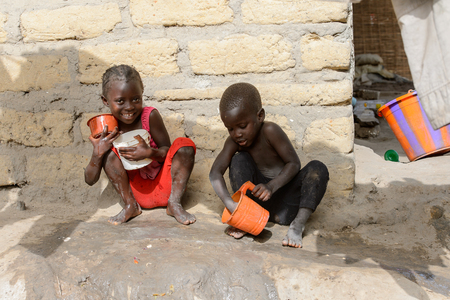 ORANGO ISLAND, GUINEA BISSAU - MAY 3, 2017: Unidentified local children play with toy buckets in the Etigoca village. People in G.-Bissau suffer of poverty due to the bad economy Editorial