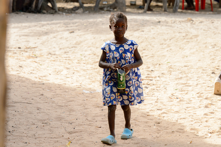 ORANGO ISLAND, GUINEA BISSAU - MAY 3, 2017: Unidentified local little girl walks along the street in the Etigoca village. People in G.-Bissau suffer of poverty due to the bad economy
