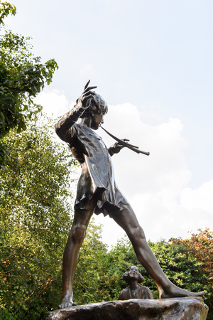 LONDON, ENGLAND - JULY 23, 2016: Peter Pan statue in the Kensigton Gardens. Peter Pan is a fictional character made by Scottish novelist  J. M. Barrie.