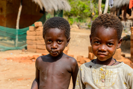 SOGA, GUINEA BISSAU - MAY 5, 2017: Unidentified local children walk along the street in a village of the Soga island. People in G.-Bissau still suffer of poverty