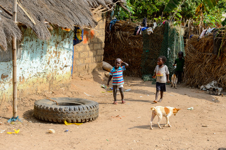 SOGA, GUINEA BISSAU - MAY 5, 2017: Unidentified local children play in the yard in a village of the Soga island. People in G.-Bissau still suffer of poverty