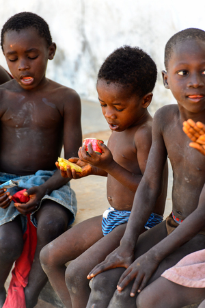 BUBAQUE, GUINEA BISSAU - MAY 5, 2017: Unidentified local children sit at the causeway in a village of the Bubaque island. People in G.-Bissau still suffer of poverty