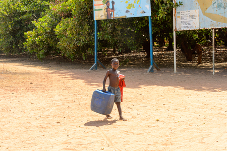 BUBAQUE, GUINEA BISSAU - MAY 5, 2017: Unidentified local little boy carries a jerrycan in a village of the Bubaque island. People in G.-Bissau still suffer of poverty Редакционное