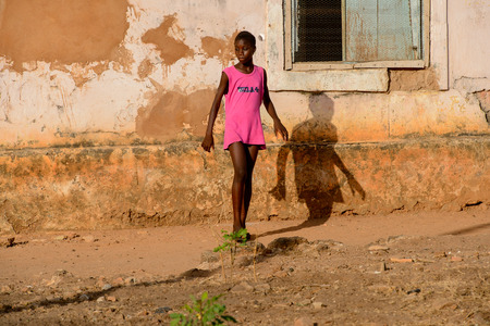 BOLAMA ISLAND, GUINEA BISSAU - MAY 6, 2017: Unidentified local girl in pink dress walks along the street in the ghost town of Bolama, the former capital of Portuguese Guinea