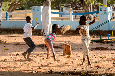 BOLAMA ISLAND, GUINEA BISSAU - MAY 6, 2017: Unidentified local children play on the street in the ghost town of Bolama, the former capital of Portuguese Guinea