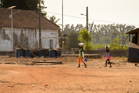 BOLAMA ISLAND, GUINEA BISSAU - MAY 6, 2017: Unidentified local woman walks with a package of water on her head in the ghost town of Bolama, the former capital of Portuguese Guinea