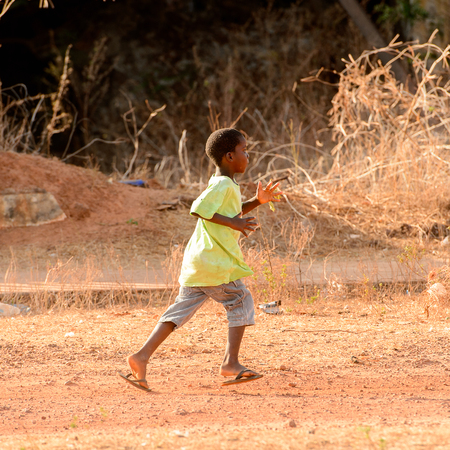 BOLAMA ISLAND, GUINEA BISSAU - MAY 6, 2017: Unidentified local little boy runs along the street in the ghost town of Bolama, the former capital of Portuguese Guinea