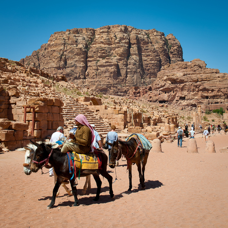 PETRA, JORDAN - APR 29, 2014: Unidentified man rides a donkey in Petra. The city of Petra was lost for over 1000 years. Now one of the Seven Wonders of the Word