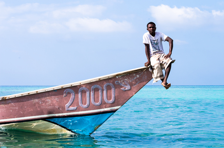 SOCOTRA, YEMEN - JAN 12, 2014: Unidentified Yemeni man sits ion a boat on the beach of the Island of Socotra. Socotra Island is a UNESCO World Heritage Site