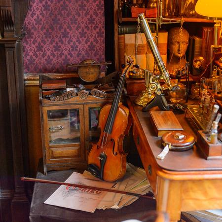 LONDON, ENGLAND - JUL 22, 2016: Violin in the Sherlock Holmes Museum, 221 Baker Street, London. Sherlock Holmes  is a fictional private detective created by Sir Arthur Conan Doyle