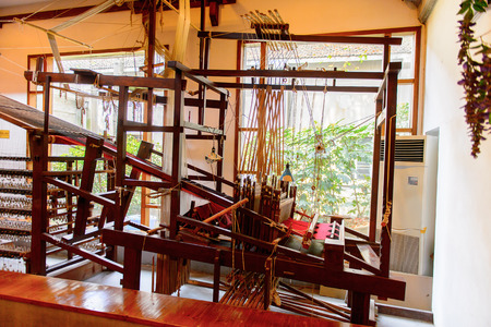 SUZHOU, CHINA - APR 1, 2016: Ancient silk making machine at the Silk museum, factory and shop in Suzhou, China. One of the popular touristic destinations