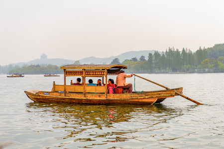 HANGZHOU, CHINA - APR 2, 2016: Traditional Chinese boat at the West Lake (Xi hu lake) is a freshwater lake in Hangzhou. UNESCO World Heritage Site (West Lake Cultural Landscape of Hangzhou)