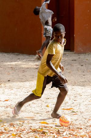 EILAND ORANGO, GUINEA BISSAU - MEI 3, 2017: Niet-geïdentificeerde lokale jongen speelt voetbal op het oranje eiland Stockfoto - 103974444