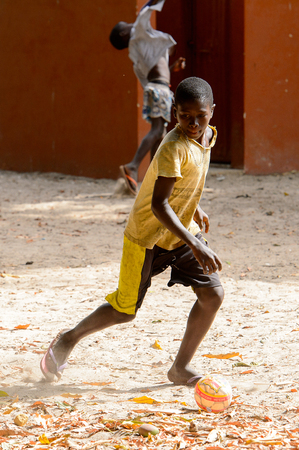 ORANGO ISLAND, GUINEA BISSAU - MAY 3, 2017: Unidentified local boy plays football on the Orange island