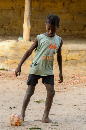ORANGO ISLAND, GUINEA BISSAU - MAY 3, 2017: Unidentified local little boy in holey shirt plays football on the Orange island