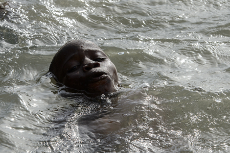 RUBANE, GUINEA BISSAU - MAY 4, 2017: Unidentified local boy swims in water during a high tide