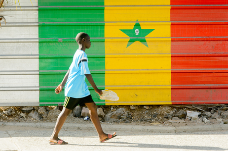 DAKAR, SENEGAL - APR 23, 2017: Unidentified Senegalese boy walks with a pair of shoes in front of the wall with tricolour flag in Dakar, the capital and main city of Senegal