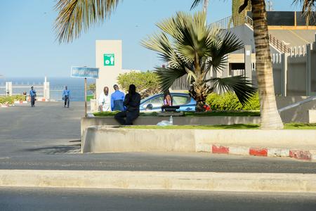DAKAR, SENEGAL - APR 23, 2017: Unidentified Senegalese people walk  on the coast of the ocean in Dakar, the capital and main city of Senegal Редакционное