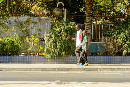 DAKAR, SENEGAL - APR 23, 2017: Unidentified Senegalese man and little boy walk beside the road  in Dakar, the capital and main city of Senegal