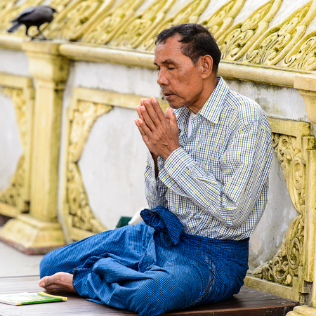 YANGON, MYANMAR - AUG 24, 2016: Unidentified Burmese man prays in a temple. 68 per cent of Myanma people belong to Bamar ethnic group