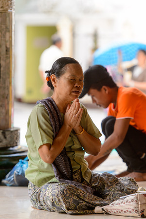 YANGON, MYANMAR - AUG 24, 2016: Unidentified Burmese woman prays in a temple. 68 per cent of Myanma people belong to Bamar ethnic group
