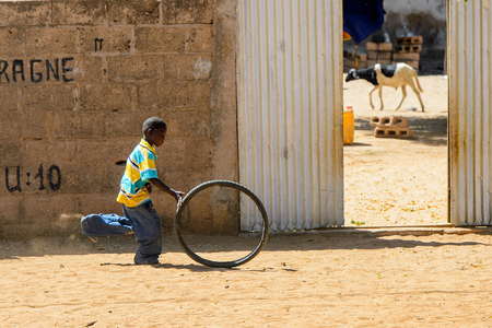 ROAD TO LAMPOUL, SENEGAL - APR 23, 2017: Unidentified Senegalese little boy plays with a tire. Still many people in Senegal live in poverty