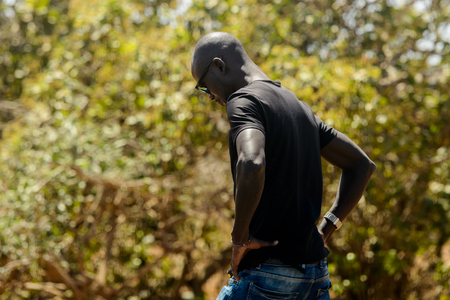 ROAD TO LAMPOUL, SENEGAL - APR 23, 2017: Unidentified Senegalese man in black shirt puts his hands on his hips. Still many people in Senegal live in poverty Editorial