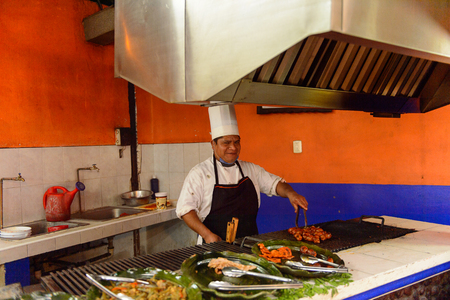 OAXACA, MÉXICO - 1 DE NOVIEMBRE DE 2016: Hombre no identificado fríe carne en el Restaurante La Choza del Chef en Oaxaca, el lugar con comida nacional mexicana