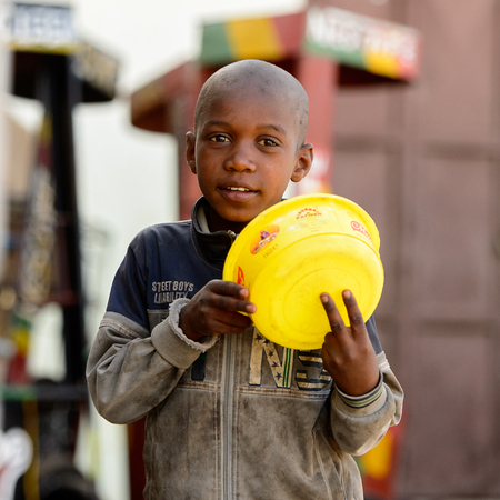 SAINT LOUIS, SENEGAL - APR 24, 2017: Unidentified Senegalese little boy holds a yellow basin in Saint Louis, one of the major cities in Senegal